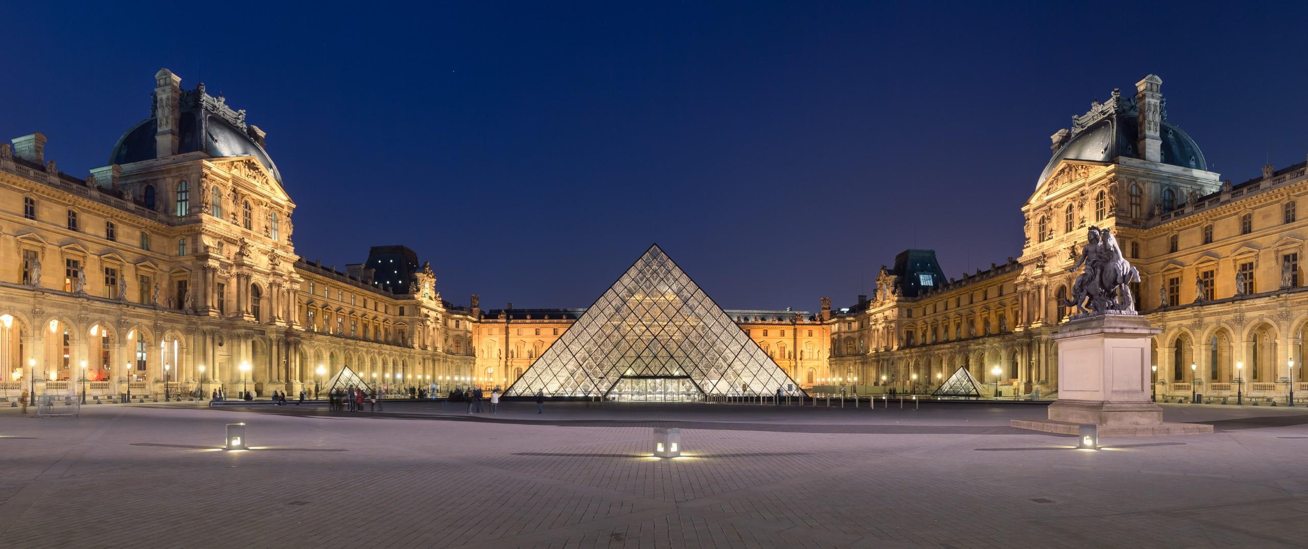 La cour Napoléon du Musée du Louvre, et sa pyramide, à la tombée de la nuit.